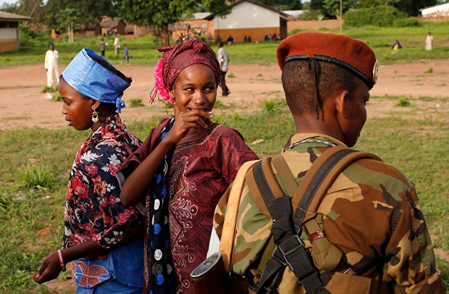 Afrikalı bir askerin önünden geçen genç kızlar.