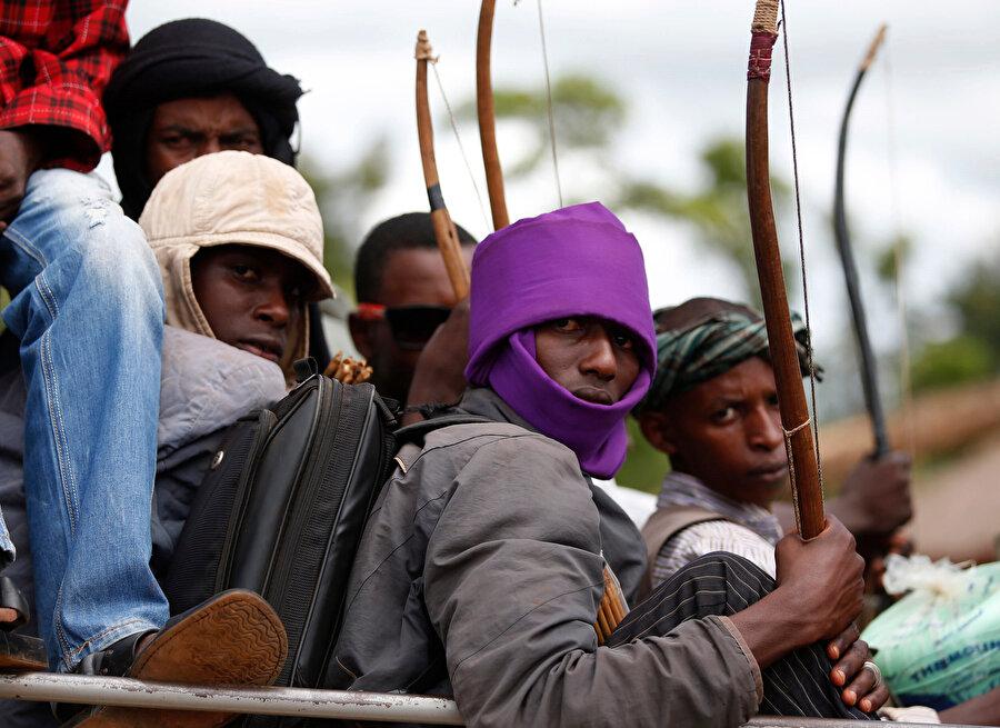 Afrikalı gençler ellerinde oklarıyla yolculuk yapıyor.