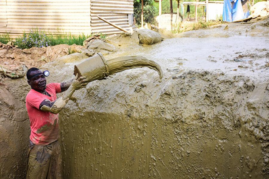 Çukurdan çamur çıkaran bir Afrikalı.