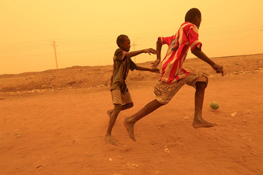 İki çocuk futbol oynuyor. Hayallerine giden yollardan biri de futbol...