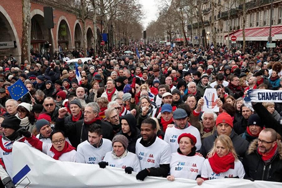 AB ve Fransa bayraklarıyla yürüyen göstericiler, 'Demokrasiye evet, devrime hayır' dövizleri taşıyor.
