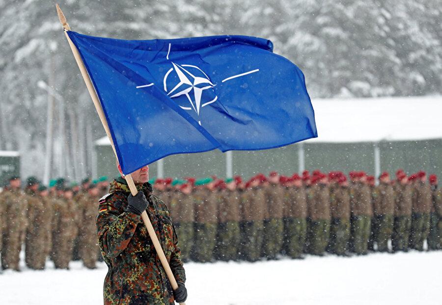 Bir asker, Alman birliklerinin ziyareti sırasında NATO bayrağını taşıyor.