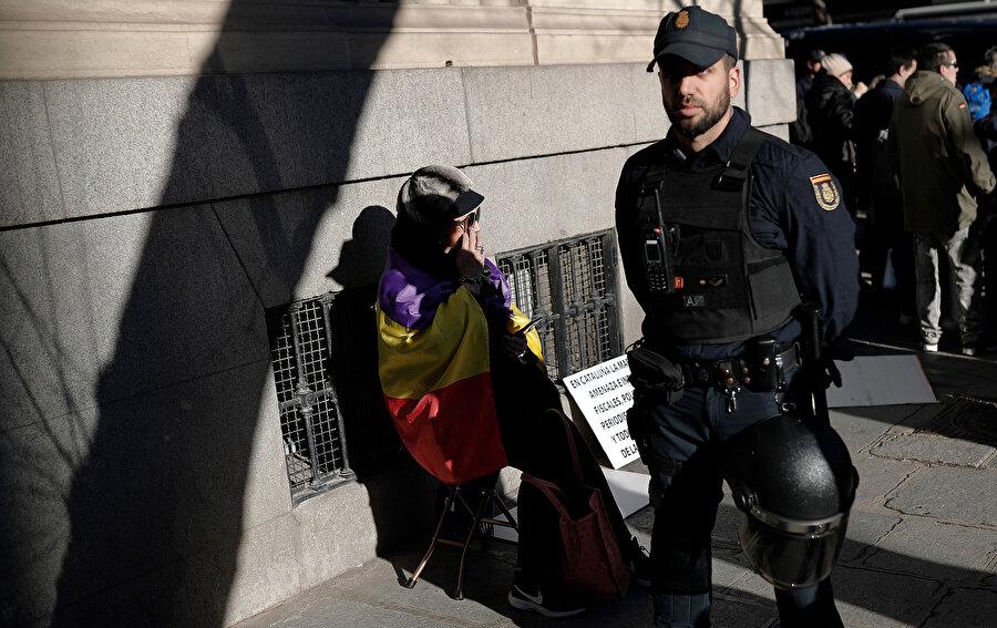 Madrid'deki Yüksek Mahkeme'nin önünde bir protestocu ve polis yan yana görünüyor.