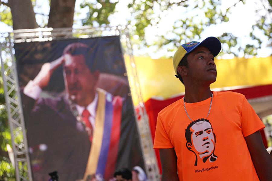 Bir genç, Venezuela eski lideri Chavez'in fotoğrafı olan bir tişörtle görünüyor.