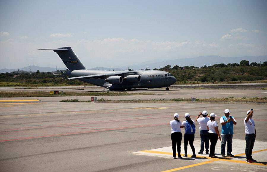 Havaalanında bekleyen kişiler ulaşan yardımların fotoğrafını çekmek için birbiriyle yarıştı.