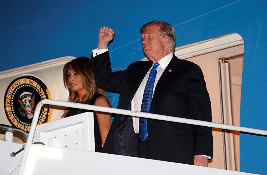 Donald Trump ve eşi Melania Trump uçaktan inerken basını selamlıyor.