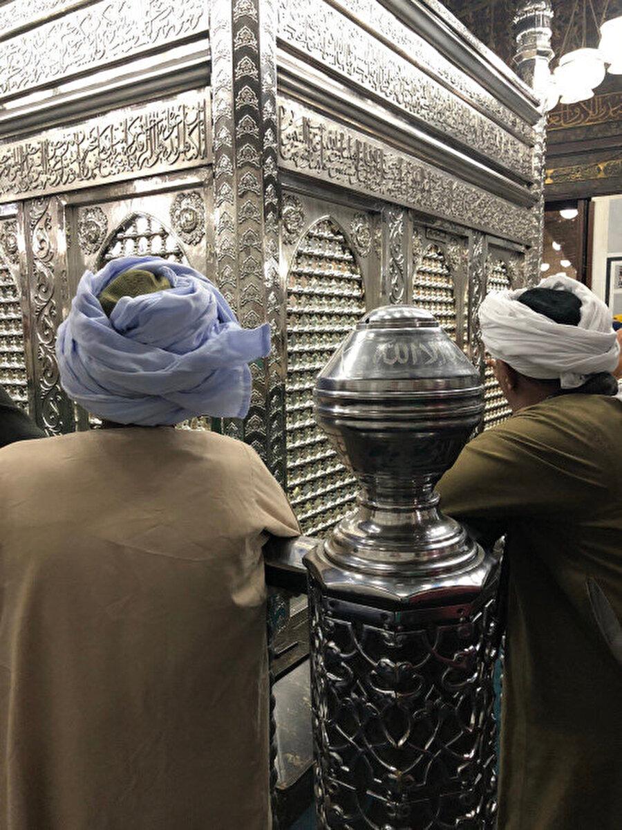 Seyyid el Hüseyin Camii içerisinde yer alan türbe ve dua eden insanlar.
