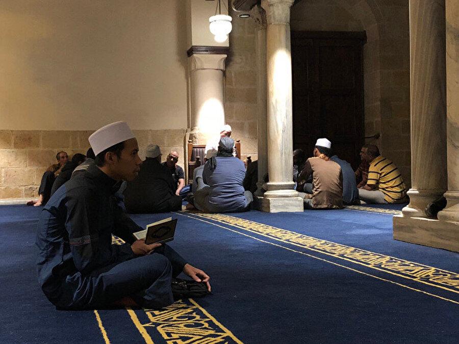 Önde Kur'an okuyan bir genç, arkada ise bir ders halkası görülüyor.