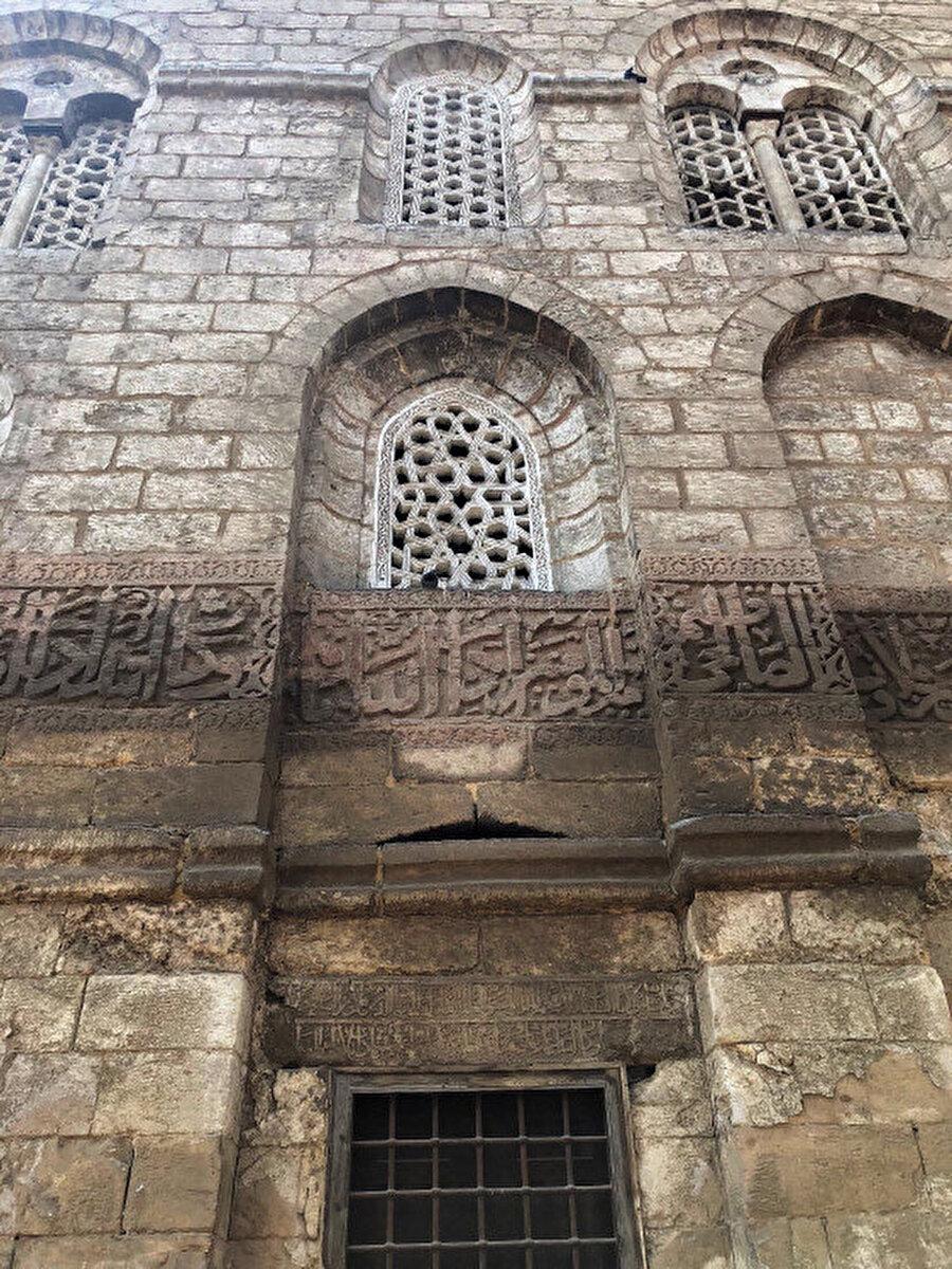 Medresenin dış cephe pencereleri ve cepheyi boydan boya kaplayan yazı şeridi.