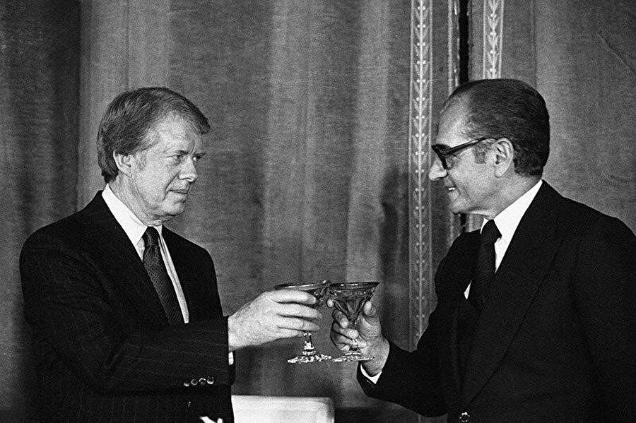 ABD Başkanı Jimmy Carter ve Muhammd Rızâ Pehlevî aralarındaki ittifakı dünya kamuoyuna kadeh tokuşturdukları bu kareyle duyurur.