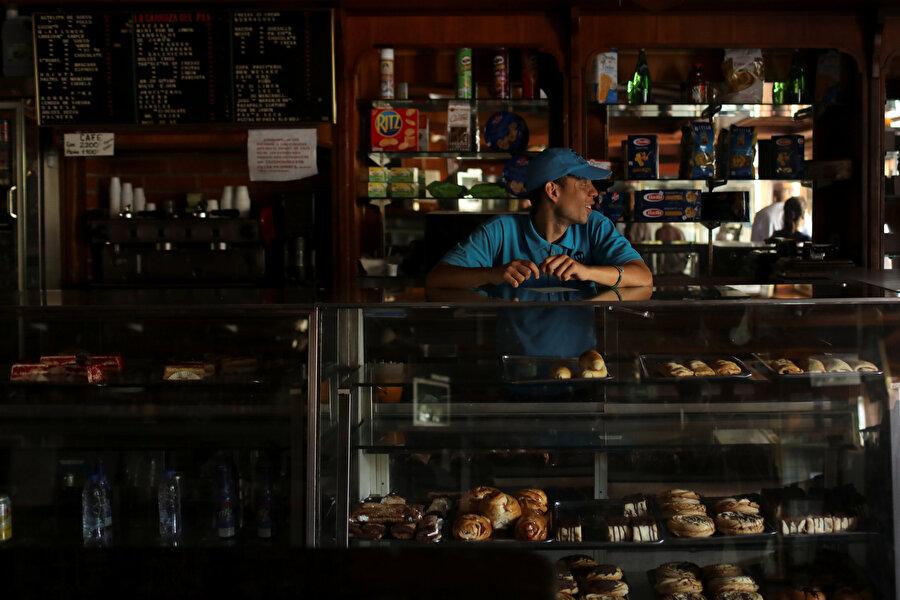 Venezuelalı bir vatandaş elektrikleri kesilen bir pastahanede müşteri bekliyor.
