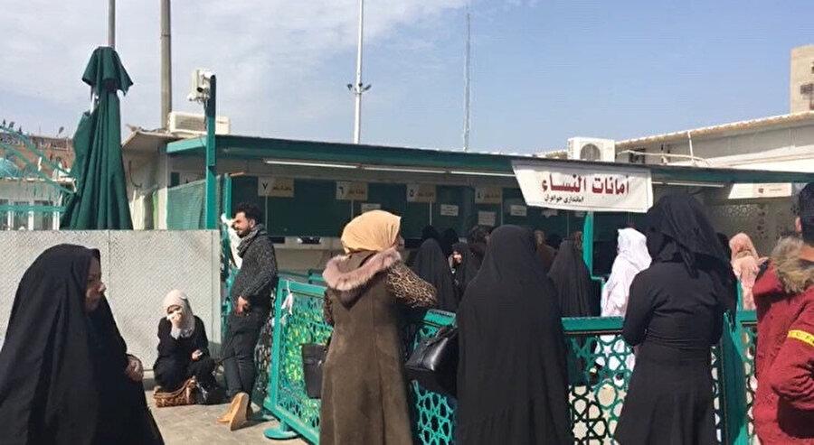 Bağdat'ın Kazımiye semtinde, İmam Musa Kazım türbesinin girişimde emanete telefon ve elektronik eşyalarını bırakmak için bekleyen kadınlar.