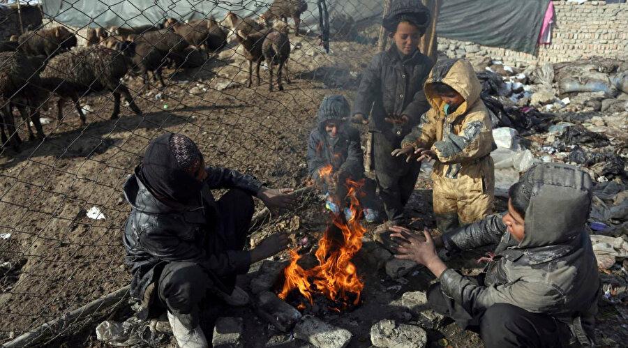 Hayvan barınağının yanındaki çöplerin arasında ısınmaya çalışan Afgan çocuklar.