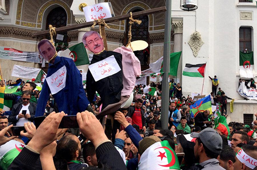 Cezayirli işadamı Ali Haddad ve eski başbakan Ahmed Ouyahia'nın temsili olarak asıldığı gösteriler.