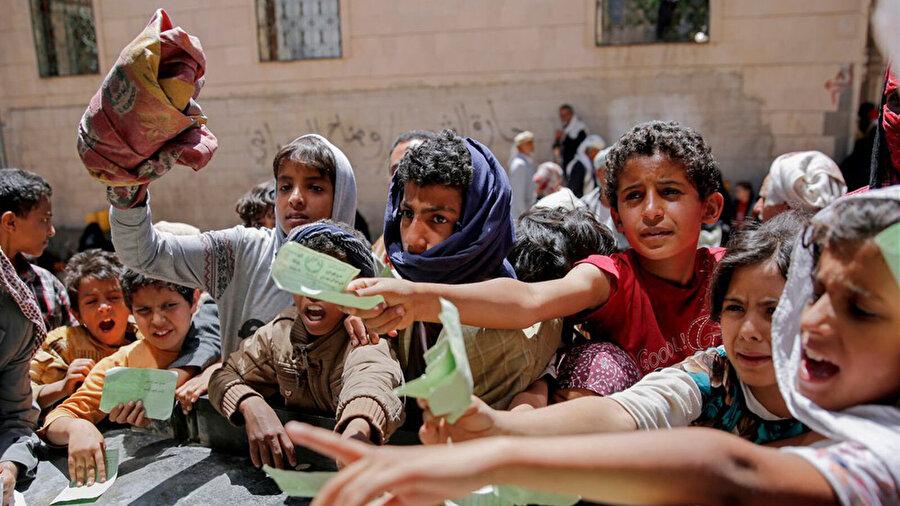 Yemen'de vakıflar tarafından dağıtılan gıda yardımlarından almak için sıra bekleyen çocuklar.