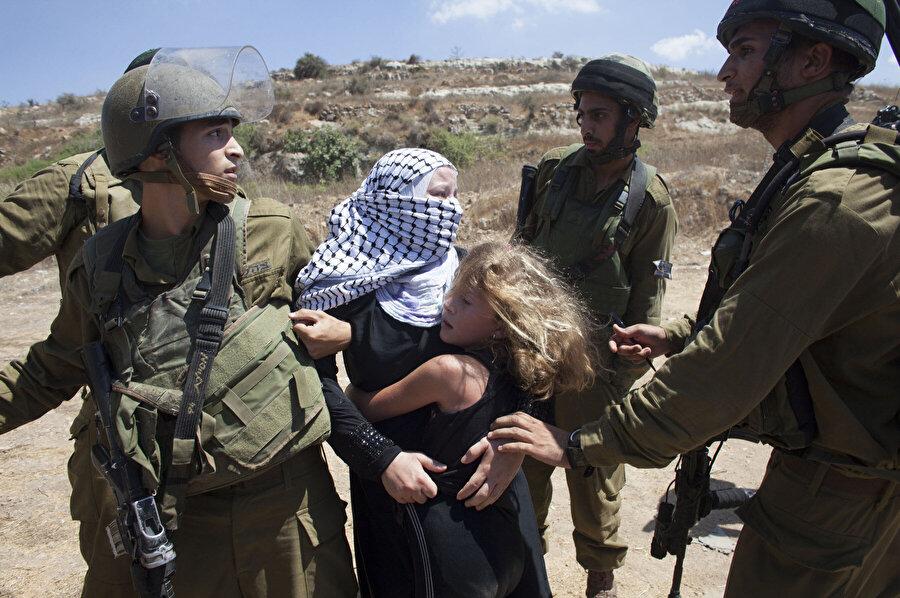 İsrail askerlerince gözaltına alınan Filistinli kadın.