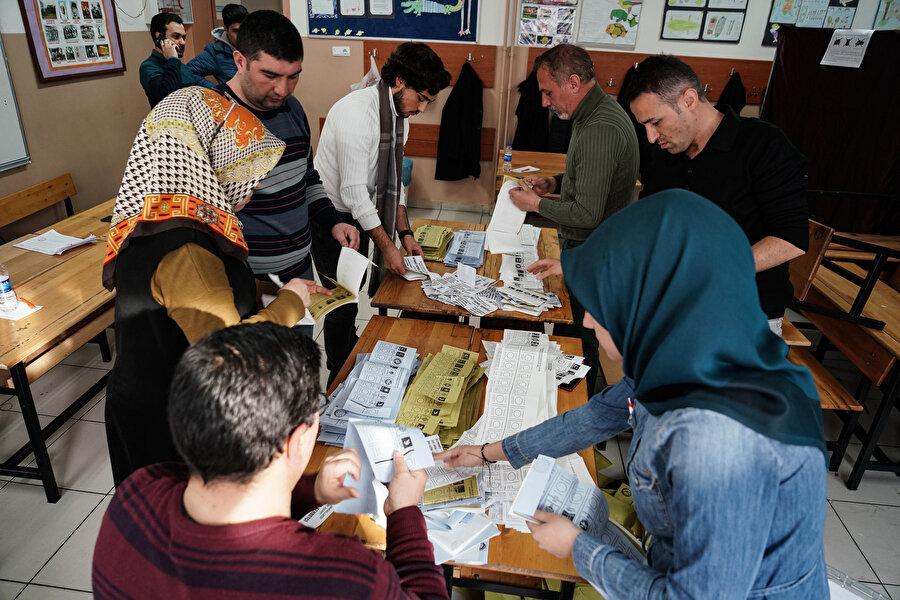 Sandık görevlileri oy sayımı sırasında görülüyor.