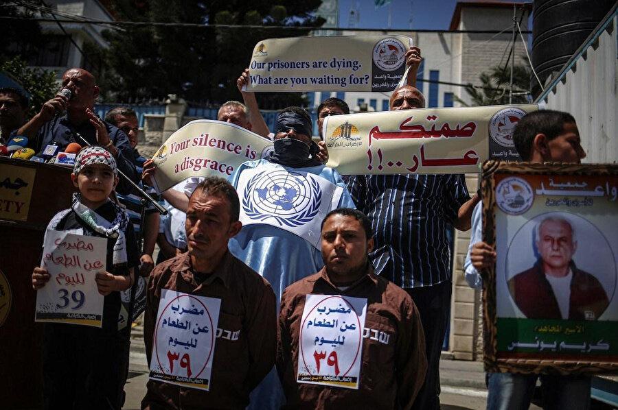 """Açlık grevine katılan Filistinli tutuklulara destek olan protestocular, üzerinde """"Filistinli tutuklular ölüyor. Siz neyi bekliyorsunuz?"""", """"Sessiz kalmanız rezalet"""" gibi ifadeler içeren pankartlar tuttu."""