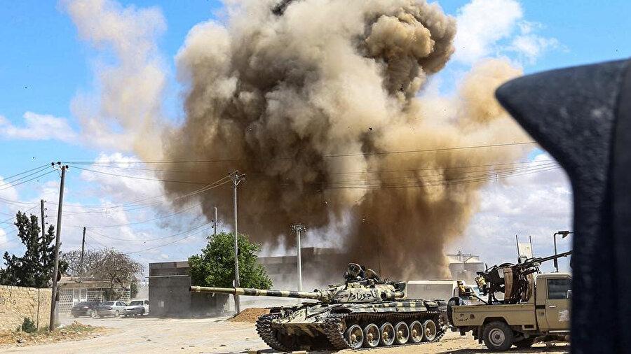 12 Nisan'da başkent Trablus'un 30 kilometre güneyindeki Vadi Rabi kırsalındaki çatışmalar esnasında çekilen bu fotoğrafta, Ulusal Mutabakat Hükumeti'ne ait tank ve araç gereçlerin arkasında hava saldırısı sebebiyle yükselen dumanlar görülüyor.