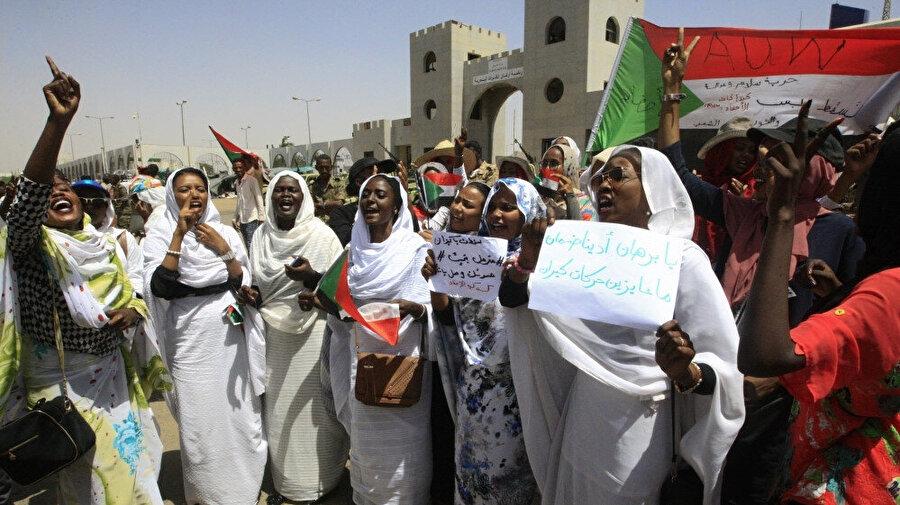 Genelkurmay karargahı önünde ulusal bayraklar ve pankartlar taşıyan Sudanlı kadınlar.