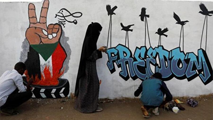 Özgürlük ve demokrasi taleplerini Hartum duvarlarına resmeden Sudanlılar.