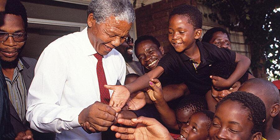 Nelson Rolihlahla Mandela'nın çocuklarla selamlaşırken çekilmiş fotoğrafı.