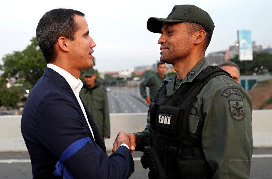 Guaido'nun da koluna mavi bant taktığı görülüyor.