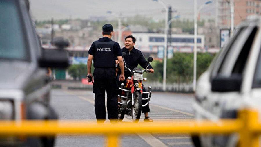 Sincan Uygur Özerk bölgesinde polis noktasında durdurulan bir Uygur, gözetleme uygulaması, polisi durdurulan kişi hakkında oldukça geniş kapsamlı bilgi toplaması için yönlendiriyor.