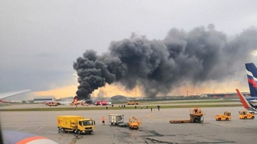 Sheremetyevo havaalanında asfaltta yanan uçaktan siyah duman çıkıyor.