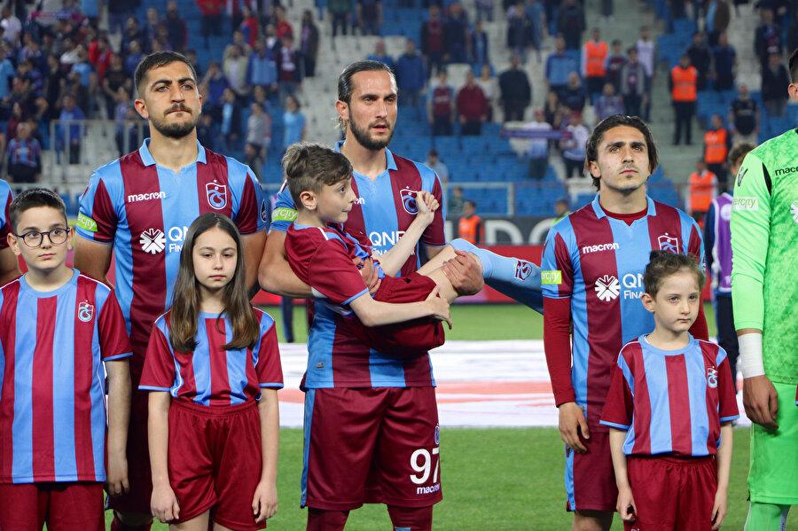 Trabzonsporlu futbolcular, seremonide miniklerle birlikte poz veriyor.