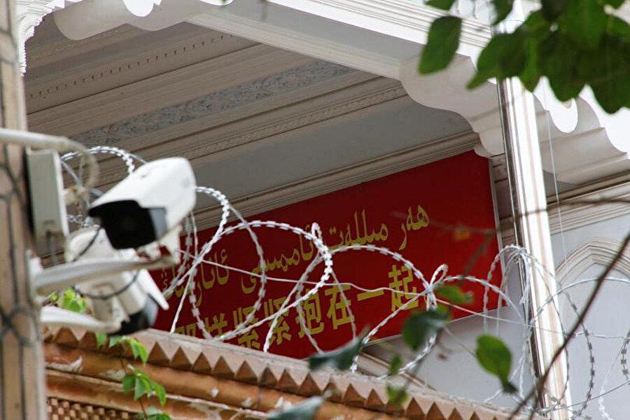 Doğu Türkistan'ın Kaşgar kentinde bir caminin kapısına yerleştirilen kamera, ibadet etmek için camiye girenleri kaydediyor.