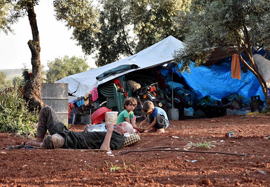 Hatay sınırında ağaçların altına sığınan Suriyeliler.