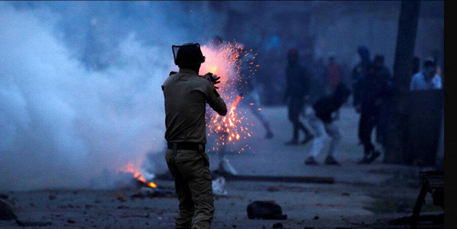 Keşmir'de ölümleri protesto eden göstericilere göz yaşartıcı bombayla müdahale eden bir Hint polisi.