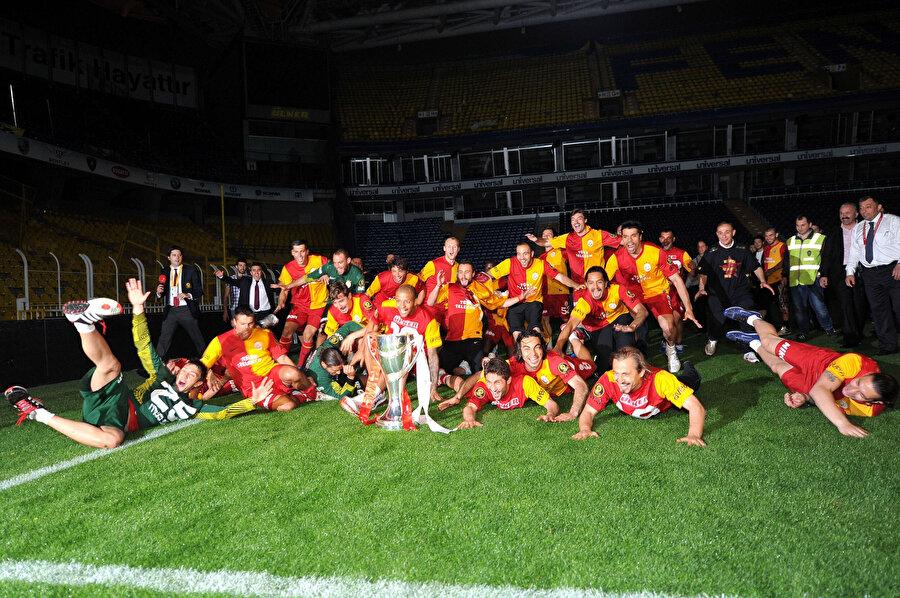 Sarı kırmızılı futbolcular, stadın ışıkları kapatılmasına rağmen kupayla veriyor.