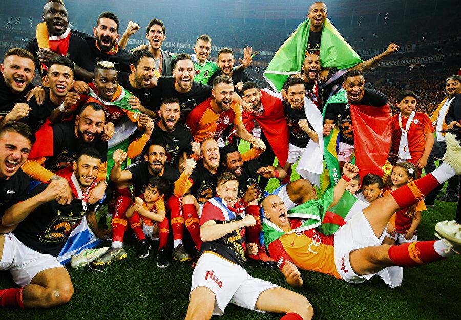Sarı kırmızılı futbolcular, 22. şampiyonluğun coşkusuyla hatıra fotoğrafı çektiriyor.