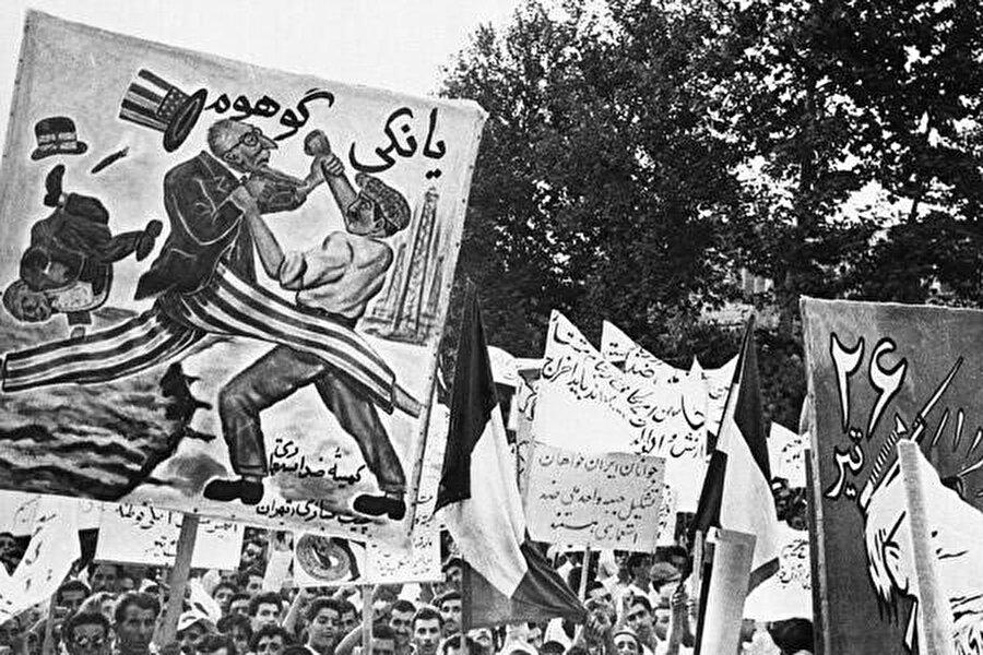 İran'daki Tudeh (Komünist) Partisi'nin üyeleri, 21 Temmuz'da Tahran'ın Parlamento Meydanı'ndaki büyük gösteri sırasında ABD'yi ve Büyük Britanya'yı kınayan afişler taşıyor.