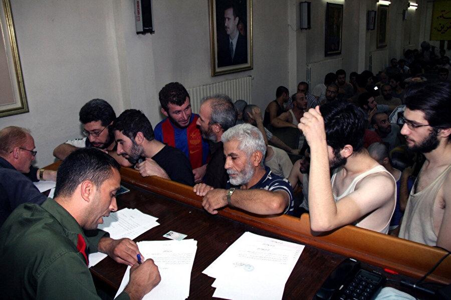 Suriyeli mahkûmlar 2012 yılında Şam Polis Kontrol Merkezi'nde serbest kalış belgelerini imzalarken. (Görsel: Bassem Tellawi / Associated Press)