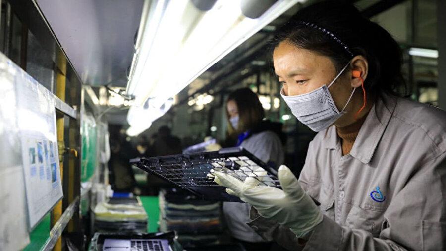 Çinli bir çalışan laboratuvarda çalışırken görünüyor.