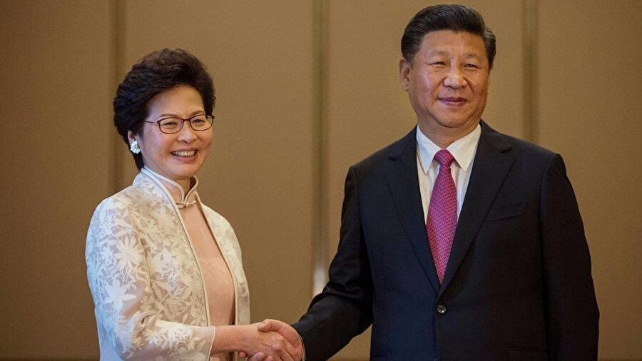 Çin'in Hong Kong Özel İdari Bölgesi'nde Mart 2017'de yapılan başyönetici seçiminden zaferle çıkan Carrie Lam, Temmuz 2017'de Çin Devlet Başkanı Şi Cinping'in (sağda) huzurunda Pekin merkezi hükümeti ve Hong Kong halkına bağlılık yemini ederek görevi selefi Leung Chun-ying'den devralmıştı.