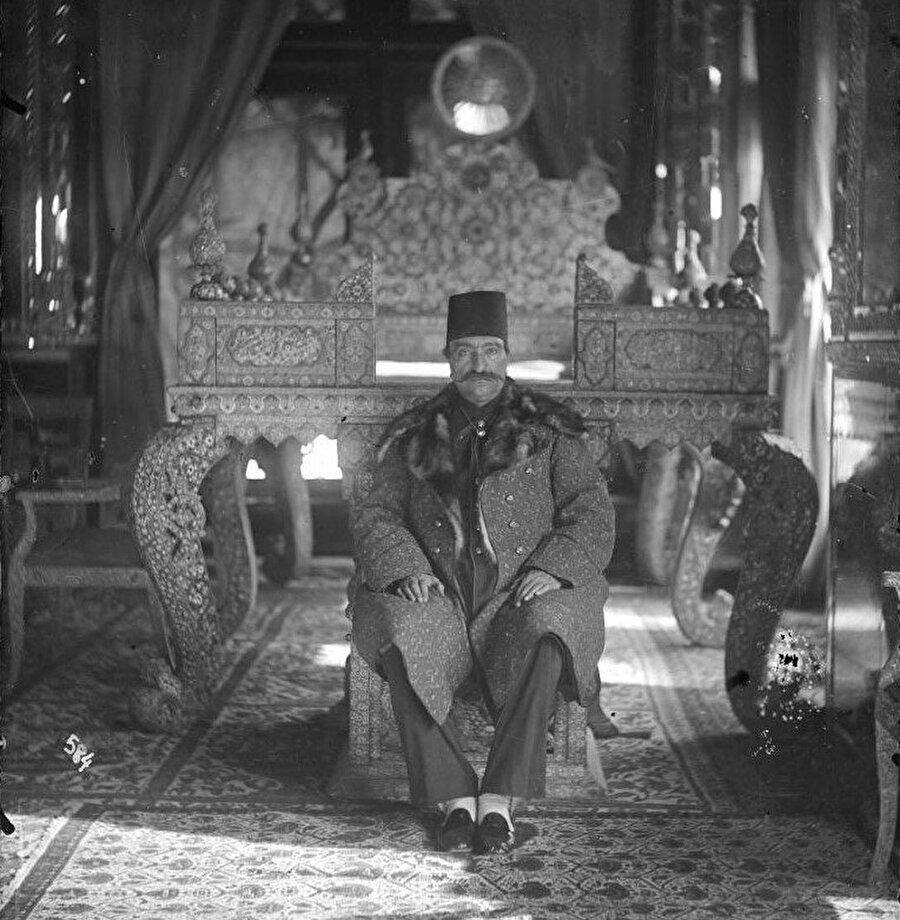 Nasirüddün Şah, Tahran'daki Gülistan Sarayı'nın Taht Odasında Tavus kuşu tahtının alt basamağında oturuyor.