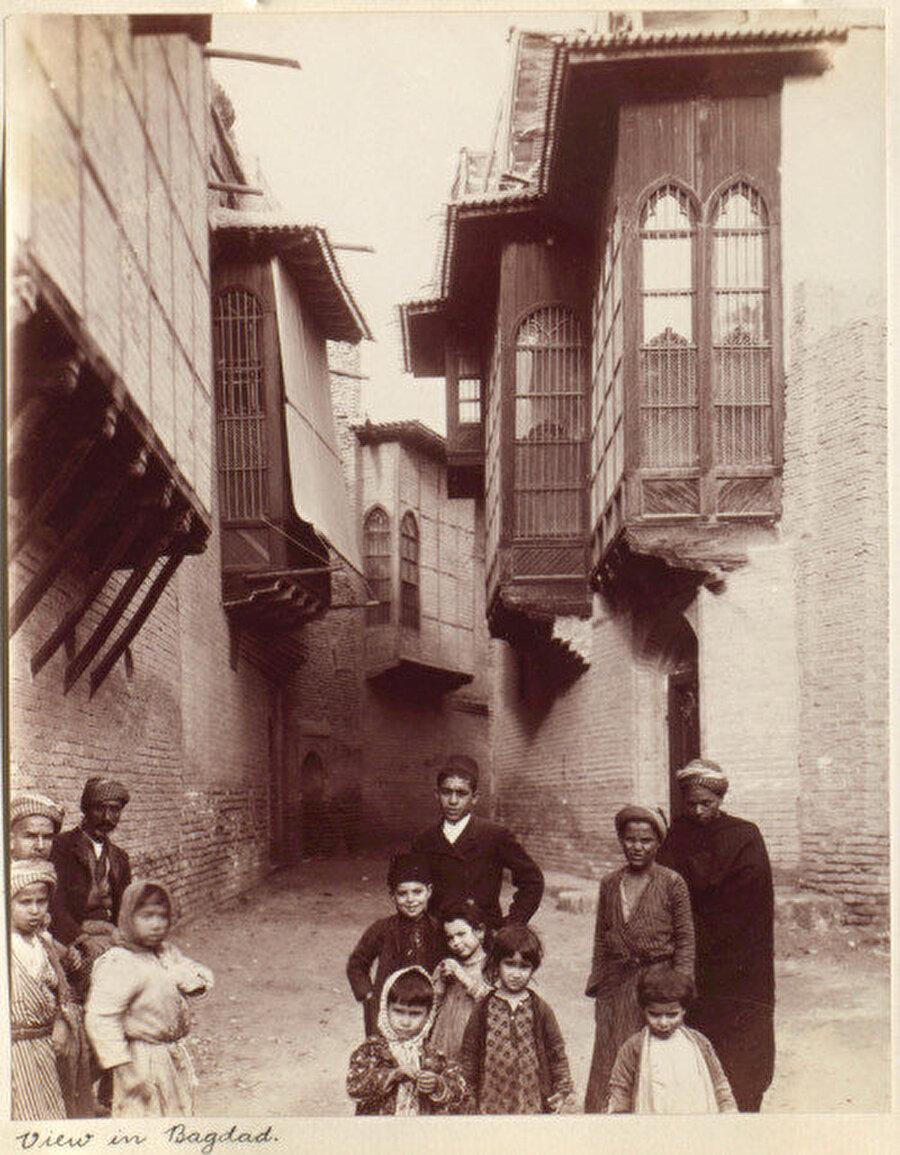 Wilfrid Malleson tarafından çekilen fotoğrafta Bağdat'ın dar sokaklarında farklı kültürlerden gelen yetişkinler ve çocuklar görülüyor, 1906.