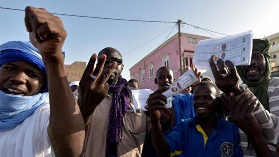 Seçmenler batı Moritanya'daki bir oy kullanma merkezinin dışında sevinç gösterilerinde bulunuyor.