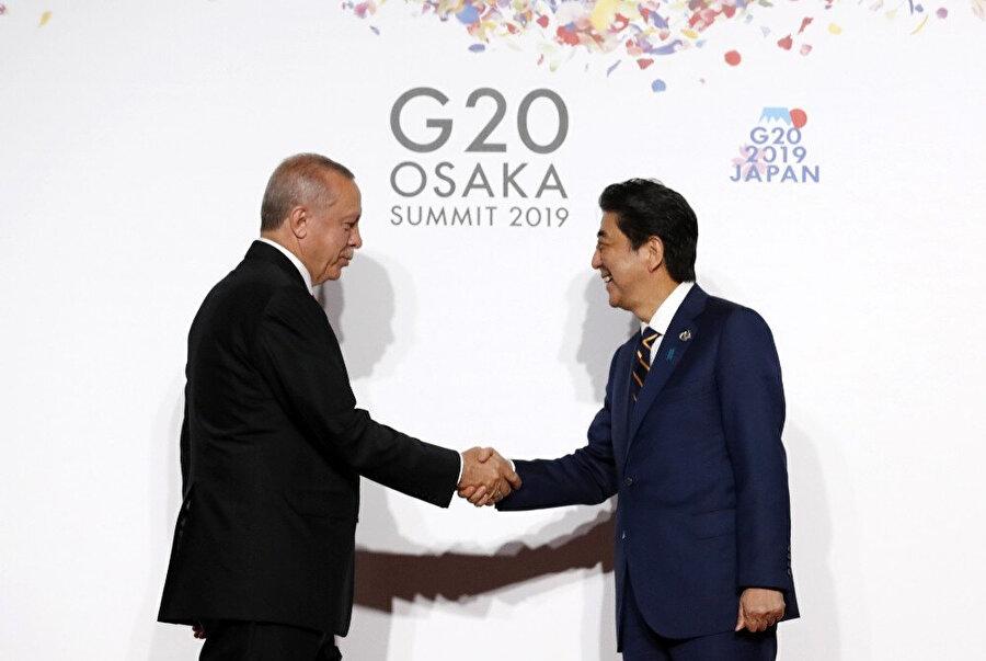 Japonya Başbakanı Şinzo Abe ve Cumhurbaşkanı Recep Tayyip Erdoğan selamlaşırken çekilen bir kare