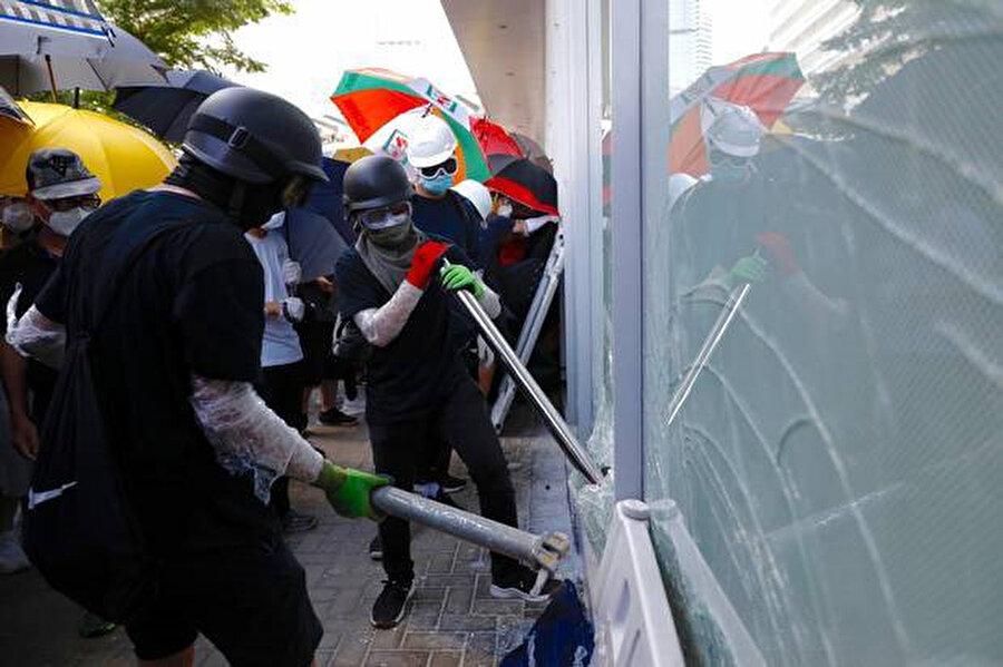 Protestocular Hong Kong'daki Yasama Konseyi'nin cam duvarlarını yıkmaya çalışıyor.