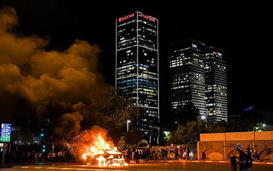 Gösteriler sırasında ateşe verilen bir araç.