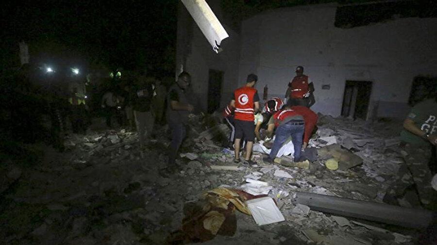 Libyalı Kızılay çalışanları, güvenlik merkezindeki hava saldırısından sonra göçmenlere ait cesetleri topladı.