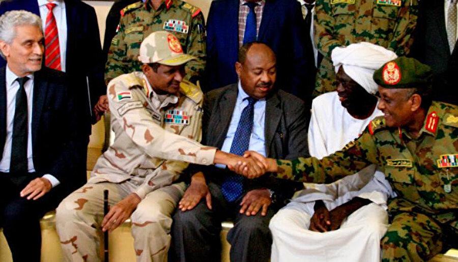 Sudan Askeri Geçiş Konseyi (AGK) Başkan Yardımcısı Muhammed Hamdan Dakalu Hmidti, (solda) Hartum'da bugün düzenlenen basın toplantısının ardından Genelkurmay Başkanı ile el sıkışırken.