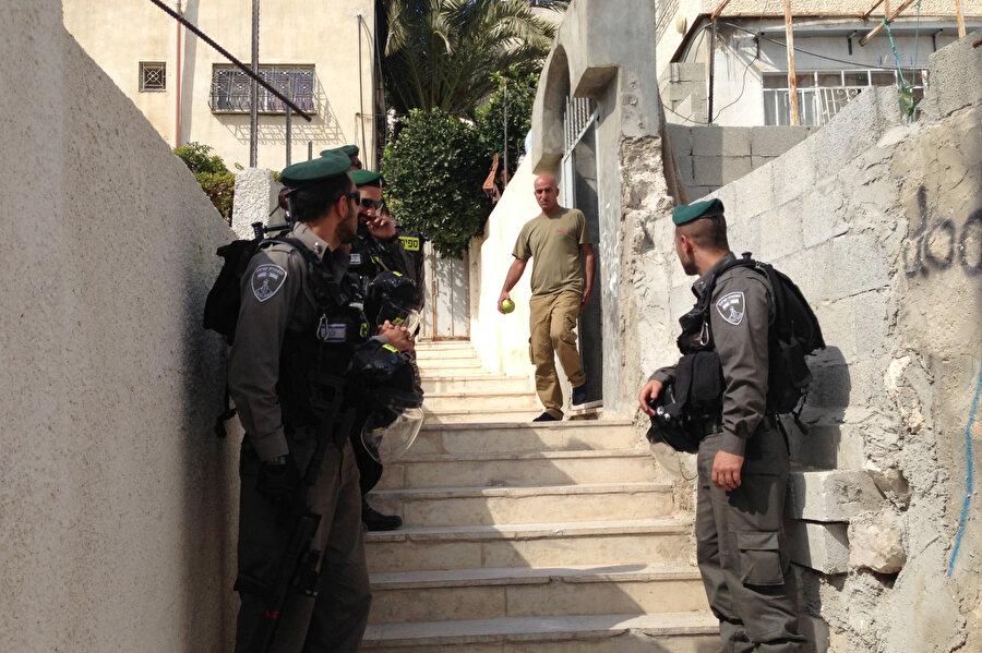 İsrail polisi, Doğu Kudüs'te yoğunlukla Filistinlilerin yaşadığı Silvan mahallesinden apartman satın alan Yahudilere ait bir evin yanında duruyor. Evi satan Filistinli, evini Filistinli bir emlakçıya verdiğini asıl sahibinin bir Yahudi olduğunu bilmeden evi sattığını belirtiyor.