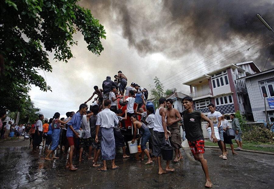 2012 yılında Budistler ile Müslümanlar arasında çıkan çatışmalar sırasında yanan evlerini söndürmek için itfaiye aracının başına toplanan Arakanlı Müslümanlar.