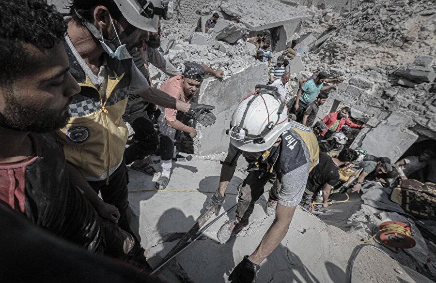 Esed rejiminin İdlib'e düzenlediği hava saldırısı sonrası görevliler, arama-kurtarma çalışmaları yürütüyor.